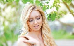 可爱的柔和的妇女在春天花卉庭院里 免版税图库摄影