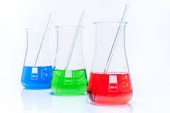套有颜色液体的三个圆锥形温度抗性烧瓶 免版税库存图片