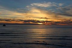 多云天空和日落在俄勒冈沿岸航行太平洋岩石露出 免版税库存照片