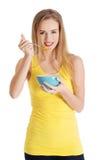 吃谷物的愉快的白肤金发的妇女 库存照片