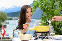 吃瑞士乳酪涮制菜肴的人们吃晚餐 免版税图库摄影