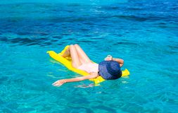 放松在可膨胀的床垫的妇女在清楚的海 库存图片