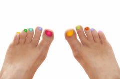 与在白色隔绝的彩虹五颜六色的钉子的女孩脚 免版税库存图片