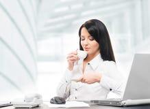 年轻和可爱的女实业家饮用的早晨咖啡 免版税库存照片