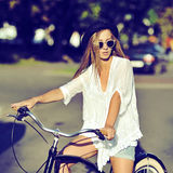 一辆减速火箭的自行车的时髦的年轻行家妇女 室外的方式 库存图片