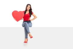 拿着红色心脏的美丽的女孩供以座位在盘区 免版税库存照片