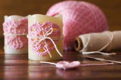 与桃红色钩针编织手工制造心脏的两个蜡烛圣徒华伦泰的 库存照片