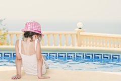 女孩池坐的年轻人 库存图片
