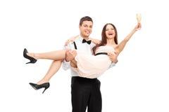 年轻夫妇饮用的香槟和有乐趣 免版税库存照片
