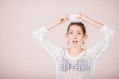 Удивленная женщина с чашкой и поддонником Стоковое Изображение RF