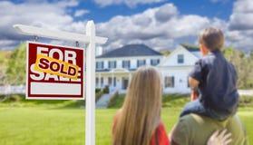 为销售房地产标志和议院卖的家庭面对 图库摄影
