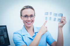 Усмехаясь женский дантист указывая на рентгеновский снимок Стоковые Изображения