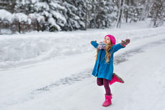 小女孩在一件蓝色外套穿戴了和一个桃红色帽子和起动,跑与被伸出的胳膊到边在冬天森林里 图库摄影