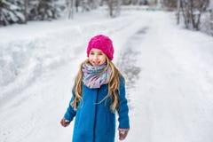 一个逗人喜爱的小女孩的画象有长的金发的,穿戴在一件蓝色外套和一个桃红色帽子在冬天森林里 库存图片