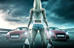 性感的白肤金发的妇女手拿着旗子-开始赛跑 库存照片