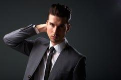 西装的时髦的年轻人用在头发的手 免版税库存图片