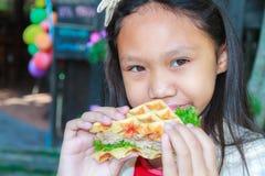 Το κορίτσι παιδιών τρώει το χοιρινό κρέας βαφλών Στοκ Φωτογραφίες