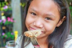 Το κορίτσι παιδιών τρώει το χοιρινό κρέας χάμπουργκερ Στοκ εικόνες με δικαίωμα ελεύθερης χρήσης