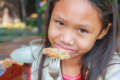 Το κορίτσι παιδιών τρώει το χοιρινό κρέας χάμπουργκερ Στοκ Εικόνες