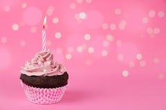 与光的桃红色生日杯形蛋糕 免版税库存图片