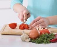 烹调在新的厨房里的妇女做与蔬菜的健康食物 免版税库存照片
