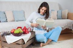 年轻可爱的妇女,在家读书,吃结果实 免版税库存图片