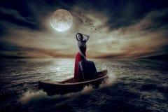 带着站立在一条小船的手提箱的时髦的妇女在海洋的中部 免版税库存照片