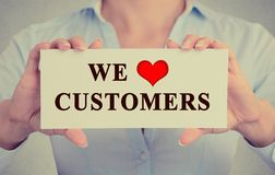 图象女实业家递拿着与我们爱顾客的消息的标志 图库摄影