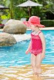 在游泳池附近的滑稽的小孩女孩在热带手段在泰国,普吉岛 免版税库存照片