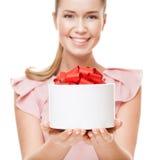 有一件礼物的年轻愉快的微笑的妇女在手上 在礼物的焦点 库存图片