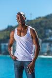 Αφρικανικός μαύρος που φορά την άσπρη φανέλλα και τα μπλε κοντά τζιν Στοκ Εικόνες