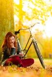妇女在使用片剂计算机读书的秋天公园 免版税图库摄影