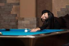 Женщина играя бассейн около для того чтобы ударить шарик Стоковое Изображение