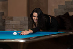 Усмехаясь счастливая женщина играя биллиард Стоковые Фото