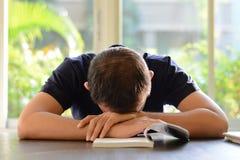 睡觉在与被打开的书的桌上的年轻人 免版税库存图片