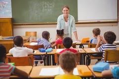 俏丽的老师谈话与年轻学生在教室 免版税库存图片