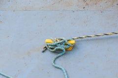 老蓝色绳索被栓染黄在具体码头的磁夹板 库存图片