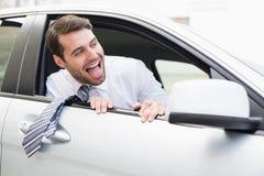 坐在驾驶席的无忧无虑的商人 免版税库存图片