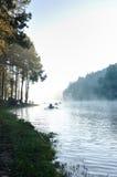 在沼泽的早晨薄雾与剪影小船 免版税库存照片