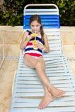 享受一份热带饮料的孩子在一个室外水池 图库摄影