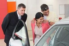显示汽车的内部的车商对夫妇 免版税库存照片