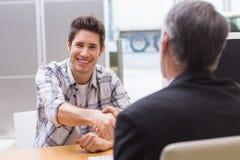 握推销员手的微笑的顾客 库存图片