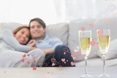 Σύνθετη εικόνα του ζεύγους που στηρίζεται σε έναν καναπέ με τα φλάουτα της σαμπάνιας Στοκ Εικόνα