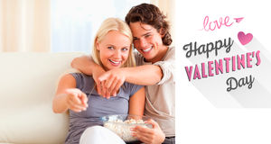 看电视的逗人喜爱的夫妇的综合图象,当吃玉米花时 库存照片