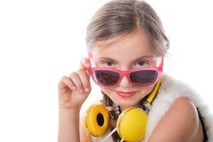 Ένα όμορφο μικρό κορίτσι με τα ρόδινα γυαλιά και τα κίτρινα ακουστικά Στοκ φωτογραφία με δικαίωμα ελεύθερης χρήσης