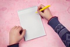 做在空白的笔记本的男性手笔记 免版税库存图片