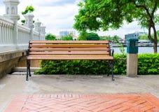长凳在河边在公园 库存图片
