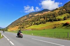 高速旅行在摩托车两骑自行车的人 库存照片