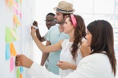 Επιχειρηματίες που γράφουν τις ιδέες σχετικά με τις κολλώδεις σημειώσεις Στοκ εικόνες με δικαίωμα ελεύθερης χρήσης