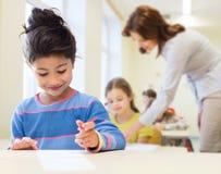 在教室背景的愉快的矮小的学校女孩 免版税库存图片